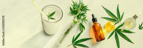 Fototapeta Cannabis milk, leaf of cannabis and a bottle of CBD Oil and tincture on the kitchen table. Top view, flat lay Banner obraz na płótnie
