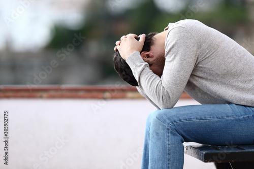 Fotografía Profile of a sad man complaining sitting on a bench