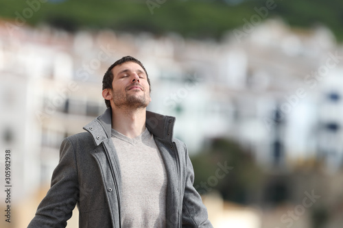 Fototapeta Adult man breaths deeply fresh air in a rural town in winter