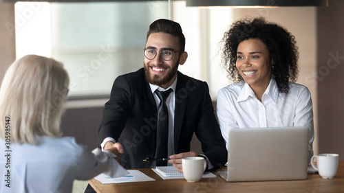 Photo Smiling multiethnic employers handshake female applicant at interview
