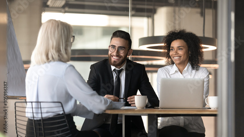 Fototapety, obrazy: Smiling multiracial employers impressed by female applicant at interview