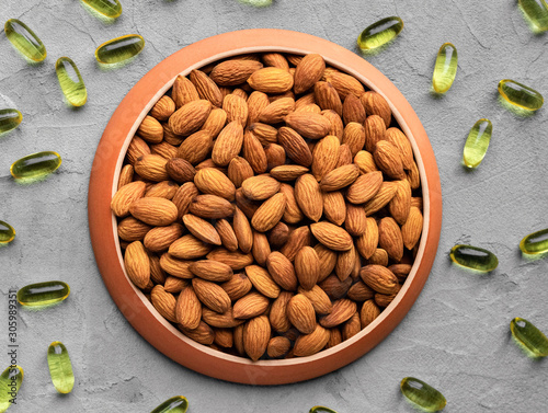Photo almonds as a source of omega fatty acids in a round plate and yellow gelatin cap