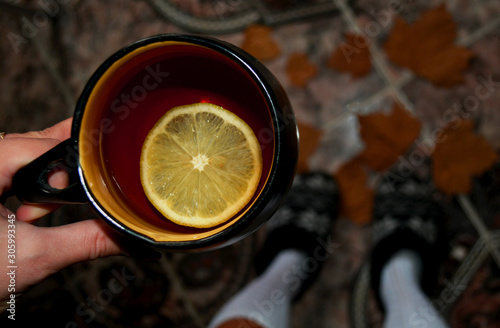 Recess Fitting Tea Cozy autumn atmosphere, a mug of hot tea with lemon on a leaf background. Direct sunlight