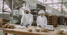 Large Capturing Video In A Big Bakery Industry Industrial Machine Bakers Working On The Table Preparing Dough For Bread