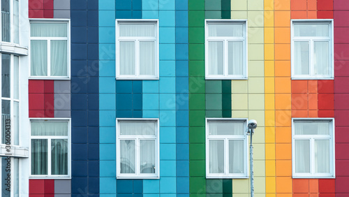 Modern bright rainbow facade of a kindergarten. Multicolor wall of a public building. Positive vibrant architecture. - fototapety na wymiar