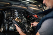 Close-up of mechanic using diagnostic tool while maintaining car engine.