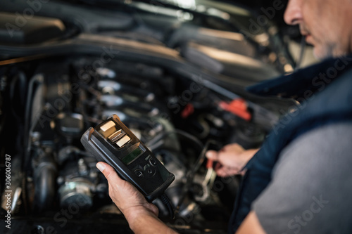 Photo Close-up of mechanic using diagnostic tool while maintaining car engine