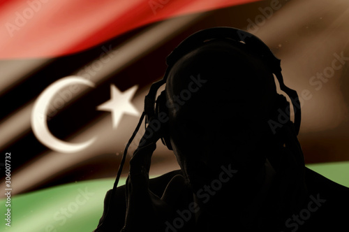 Photo  Silhouette of a man wearing headphones on the background of the flag of Libya, e