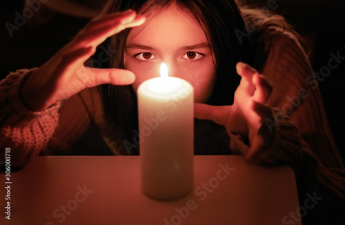Photo Yong girl fortunetelling moving her hands around candle light