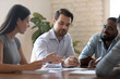Financial expert holding brainstorming meeting with multiracial engaged colleagues.