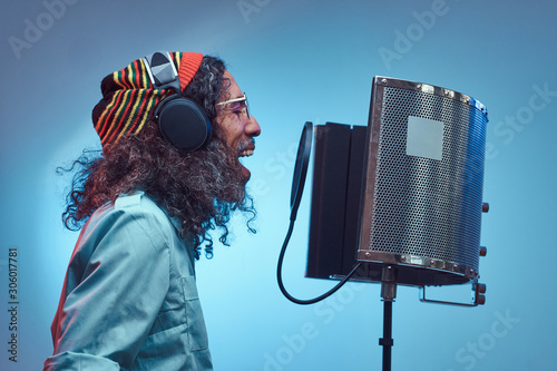 Photo  African Rastafarian singer male wearing a blue shirt and beanie emotionally writing song in the recording studio