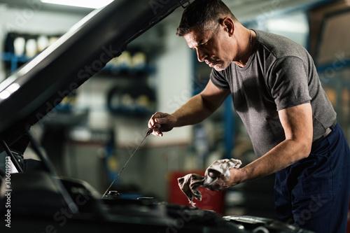 Auto mechanic checking car oil in a repair workshop.