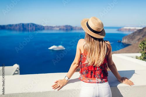 Fototapeta Woman traveler looking at Caldera from Fira or Thera, Santorini island, Greece. Tourism, traveling, vacation concept obraz