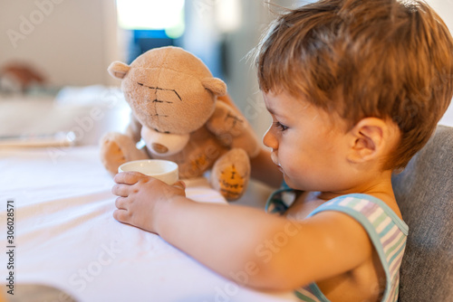 Cute little boy giving glass of milk to teddy bear. Playing with teddy bear at home. Childhood happiness concept. A boy is sitting and eating with Teddy bear. Child having breakfast.