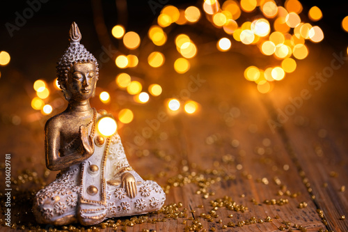 Carta da parati Buddha statue with magical lights on wooden background - Religion, Buddhism
