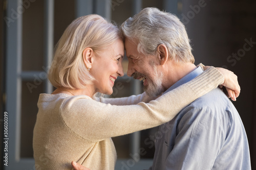 Elderly cheerful couple embracing looks at each other with love Wallpaper Mural