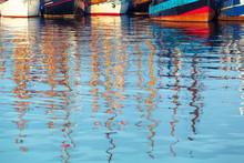 Nostalgic Ships Anchoring Detail / Row Of Vintage Ship Hulls At Harbor, Reflecting Masts At Blurred Water Surface Foreground (copy Space)