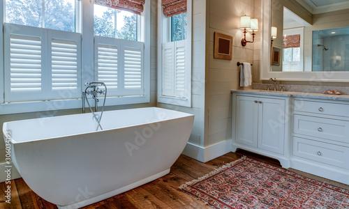 Obraz Luxury bathroom with large white tub, beautiful cabinets, and shiplap walls. - fototapety do salonu