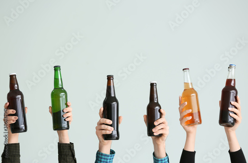 Fotografía  Hands with bottles of beer on grey background