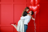 Happy young couple with heart-shaped balloons on color background. Valentine's Day celebration