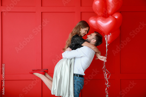 Fotografie, Tablou Happy young couple with heart-shaped balloons on color background