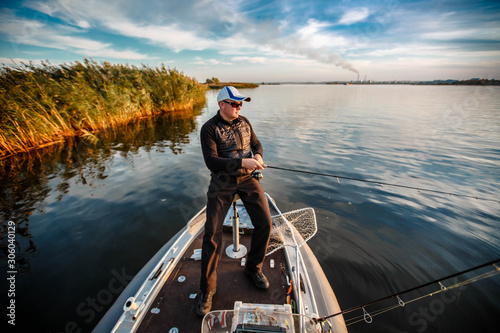 Obraz na plátne fisherman on a motor boat with spinning