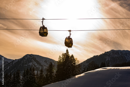 Türaufkleber Gondeln Ski lift, two gondolas against the backdrop of an orange, cloudy sky. In the background visible mountains covered with snow. Cable car at Schladming Dachstein, Austria.