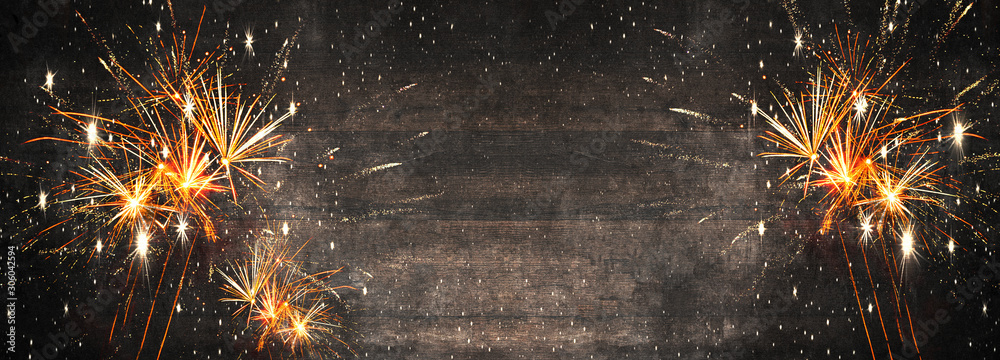 Fototapeta Silvester background panorama long - Firework on rustic brown wooden texture with space for text