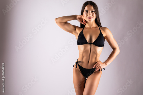 Slim body of young woman in black bikini with healthy sporty figure isolated on gray background