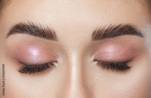 Slika na platnu Beautiful young woman with long eyelashes, beautiful fresh nude make-up, thick eyebrows and with clean skin in a beauty salon