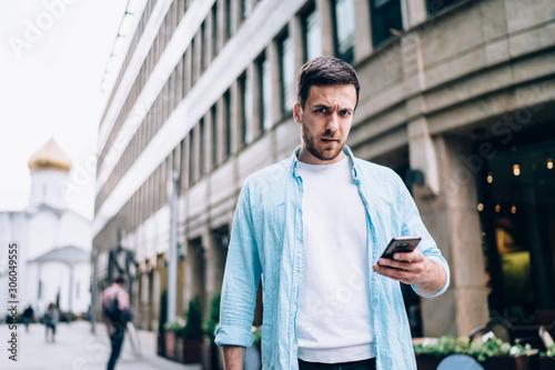 Valokuvatapetti Half length portrait of puzzled male blogger pondering on 4g internet connection