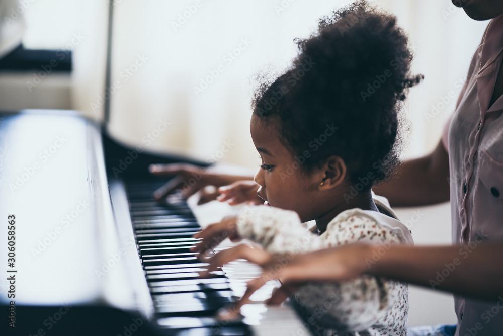 Fototapeta Mother is teaching piano tricks, African people