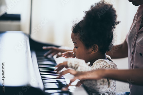 Mother is teaching piano tricks, African people Canvas Print