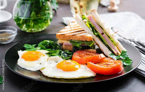 Fototapeta Breakfast: fried egg, spinach, tomatoes and club sandwich on plate. obraz