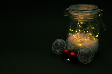 Glass Jar Full Of Lights With Christmas Tree Ornaments On A Black Background