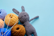 Colorful Yarn Clews With Gray Stuffed Bunny And Needles On The Blue Background. Concept Of Amigurumi Toy Making, Handcrafting, Knitting, Hobby