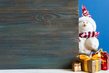 Snowman In A Snowdrift With Gifts For Christmas And New Year