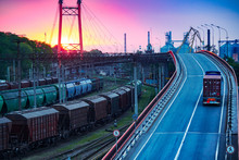 Truck With Container Rides On The Road, Railroad Transportation, Freight Cars In Industrial Seaport At Sunset