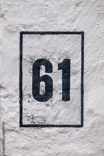 Tela  black number 61 on white wall
