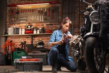 Woman Mechanic Working On A Vintage Motorbike