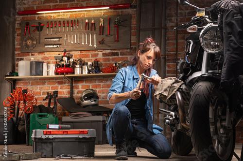 fototapeta na ścianę Woman mechanic working on a vintage motorbike
