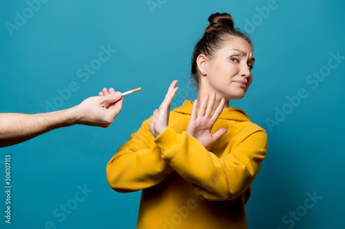 Photo girl refuses a cigarette, which a male hand holds out to her