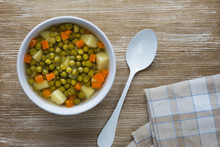 Soup With Green Peas And Vegetables In White Bowl On Wooden Background