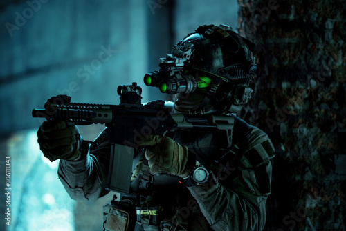 Man in uniform with machine gun and turned on night vision device inside broken building Wallpaper Mural