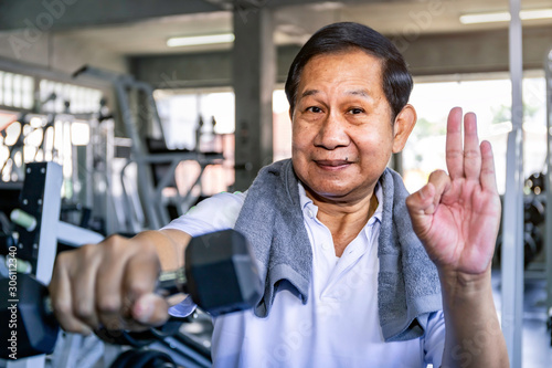 Canvastavla  Asian senior man in sportswear training with dumbbell at gym.