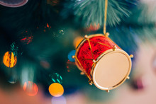Colorful Background Of Decorated Christmas Tree With Copy Space. Closeup Of Red Drum Hanging From A Decorated Christmas Tree With Blurred Background