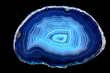 Slice Of Blue Agate Stone Specimen, With Rings Of Different Blue Shades, Against A Black Limbo Background