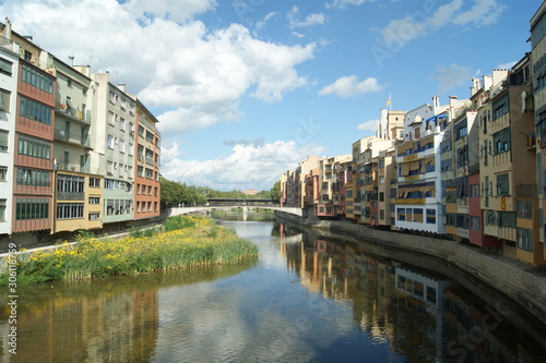 Girona, Rio Onyar. Medieval town, summers day. The old town houses by the river reflected in the still waters. Blue sky and nature and city in harmony. Colorful houses on the river bank.