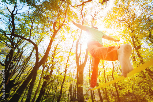 Wide angle male tightrope walker balancing barefoot on slackline in autumn forest Canvas Print