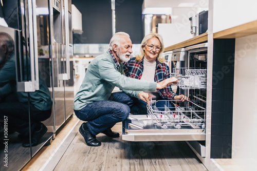 Happy senior husband and wife buying household appliances in store Canvas Print